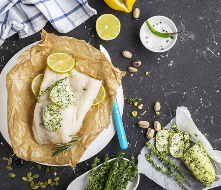 white backing: Fresh cod before baking with homemade green butter with herbs on a dark background with slices of lemon, thyme, sea salt. Top view. Healthy food concept Stock Photo