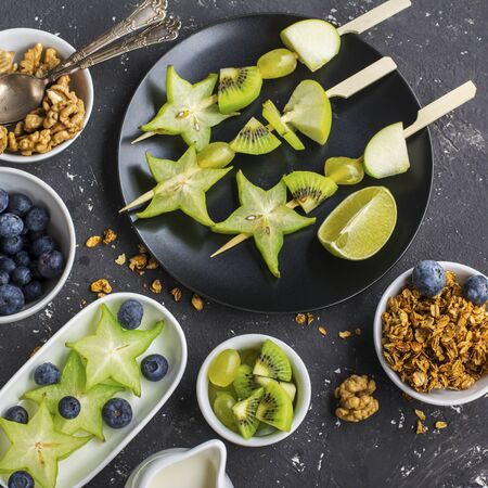 Healthy fresh breakfast. Granola, quinoa bowl, various nuts and fruit skewers with green fruits on a dark background. Top view. Color year. Greenery. Top
