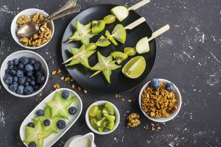 saludable desayuno fresco. Granola, cuenco quinua, varias nueces y frutas pinchos con frutos verdes sobre un fondo oscuro. Vista superior. año color. Verdor. Parte superior Foto de archivo