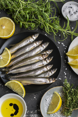 Fresh sea fish smelt or sardines ready for cooking with lomtikmi lemon, thyme, rosemary and coarse sea salt. The concept of fresh, healthy seafood. Top view