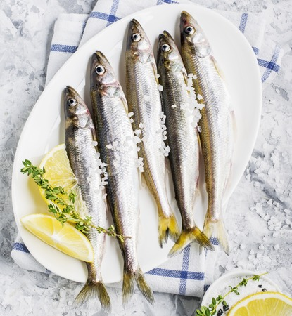 The freshest fish of the northern sea ice fishing smelt with the scent of fresh cucumber on a light background marble with lemon and herbs. Top view