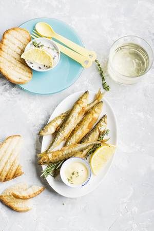 textille: Fresh sea fish deep fried smelt on marble background with slices of lemon, salt, sauce and beverage glass. Top
