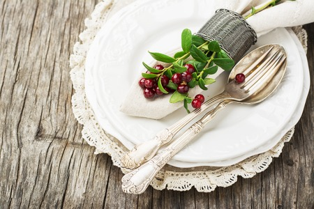 Festive table setting for dinner with German silver cutlery, spoon, fork a sprig of fresh forest cranberries. In plain gray wooden background. Top view. Hygge