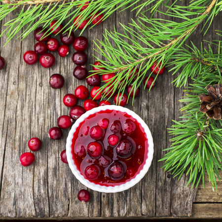 Fresh homemade cranberry sauce in a pan on dark wooden background with scattering of ripe berries. 版權商用圖片 - 68824390