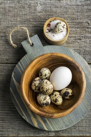 nosh: Quail eggs in a wooden bowl on  cutting board   dark background with salt. Top view
