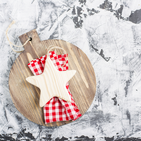 Simple Christmas background with a wooden board,  star and  fir branch on  light gray marble . Top view