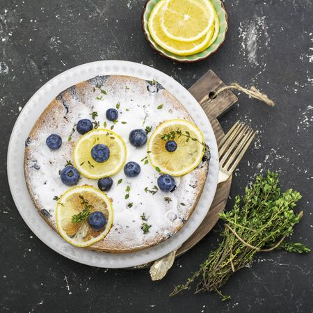 comfort food: Comfort food. Homemade flavored sponge cake with blueberries and slices of lemon on a marble background. Top Stock Photo