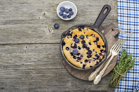 comfort food: Home comfort food. Fresh blueberry pie in a cast iron frying pan on  wooden background. Top view Stock Photo