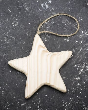 string top: Wooden handmade star on a string   simple marble dark background. Top view
