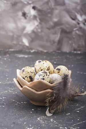 Quail eggs in the design of ceramic bowls in the form  broken shell with bird feathers on a dark marble background. selective focus Stock Photo