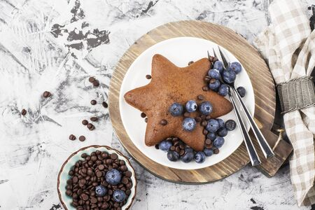 napkin ring: Homemade baking. Chocolate Biscuit star with a fresh blueberry and  drops. Top view. Flat lay Stock Photo