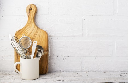 Kitchen tools, olive cutting board on a  shelf against  white brick wall. selective focus 版權商用圖片 - 68834912