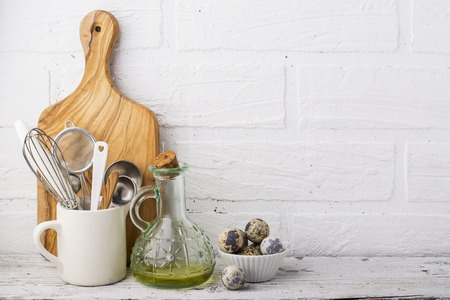 Kitchen Still Life. Olive oil in a jug, quail eggs and  tools for baking,  cutting board on  wooden shelf in the background of  white brick  wall. selective focus