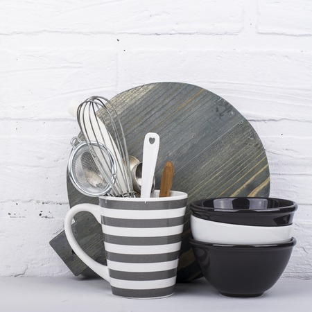 ware: Simple modern kitchen still life in monochrome marble bowls, gray striped circle, round cutting board, ceramic  against a white brick wall. The horizontal