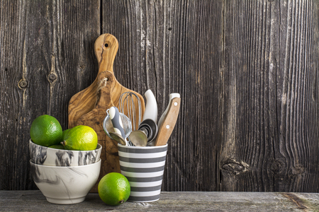 Simple kitchen still life on a background of  wooden wall   shelf with cutlery, tools, marble bowls and juicy limes. The concept  home comfort food  .