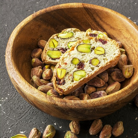 Traditional crispy Italian biscotti or cantuchini crackers with pistachios and dried cranberries in a bowl of olve wood on a dark background. Home classic healthy comfortable food