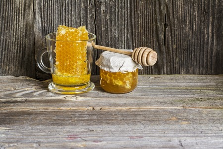 Natural organic lime honey in honeycombs with a private apiary on a textured wooden dark background in a horizontal version.