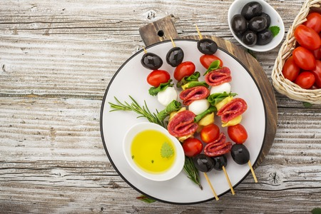 Healthy snack: mouth-watering kebabs on a picnic with tomatoes, mozzarella, salami, black olives, Basil, tortellini pasta on a cutting Board on wooden background with olive oil and herbs. From the top view. The concept of seasonal light supply. Stock Photo