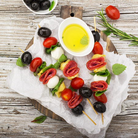 Healthy snack: mouth-watering kebabs on a picnic with tomatoes, mozzarella, salami, black olives, Basil, tortellini pasta on a cutting Board on wooden background with olive oil and herbs. From the top view. The concept of seasonal light supply. Standard-Bild