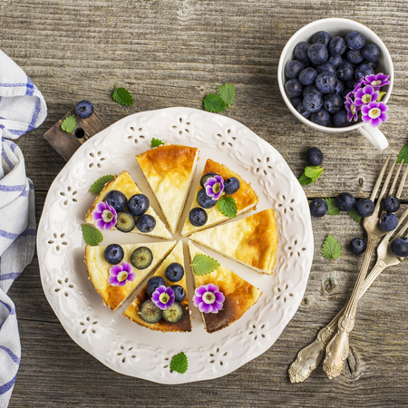 Homemade fresh cheesecake with blueberries and edible flowers on a white ceramic plate, on a simple wooden background. From the top view. The concept is helpful comfortable food
