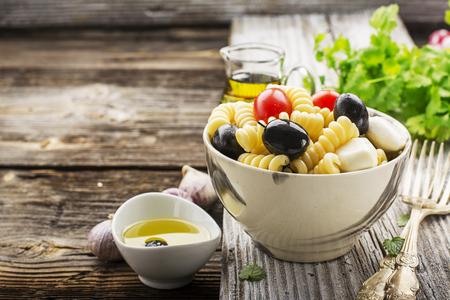 Kalter Sommernudelsalat, schwarze Oliven, Mozzarella, saftige Tomaten und tadellose Blätter in einer keramischen Marmorschüssel auf einem einfachen hölzernen Hintergrund mit Kräutern und Olivenöl, um zu dienen. Selektiver Fokus. Standard-Bild - 80122519