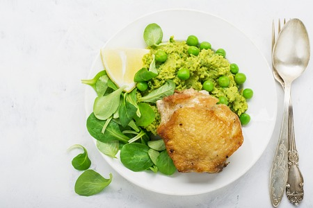 bean family: Easy healthy lunch: chicken thigh with mashed green peas and corn salad on a light background. Top view.