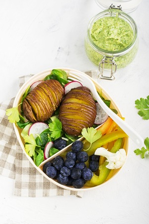 Healthy snack in a lunch box: Golden baked potatoes, salad, blueberries, green pepper, cauliflower, radish in a plastic container with a fork. Top view