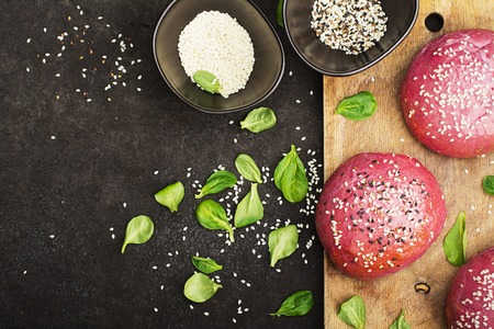 Pink buns for the vegetable Burger on the basis of beet with sesame seeds on dark background. Top view