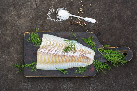 white backing: Raw cod before cooking on a black chopping Board with herbs and sea salt on a dark background. Top view Stock Photo