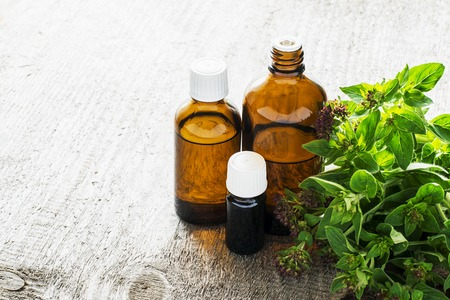 Essential oregano oil for aromatherapy in a dark glass containers on wooden background with fresh oregano. Selective focus. Banque d'images