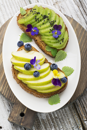violas: Healthy toast with green apple and juicy Kiwi with edible flowers of garden violas on a marble background. Color year. Greenery. Top