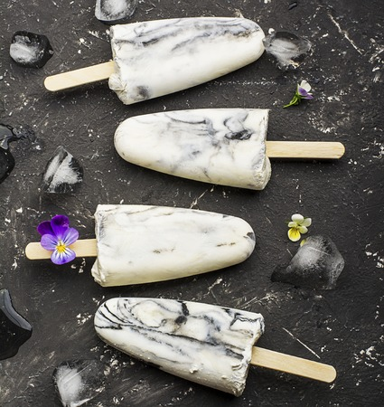 violas: Yoghurt refreshing marble ice cream popsicle in trendy fashion colors on a dark background with edible flowers of garden violas. Selective focus. Top View.