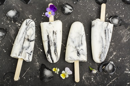 violas: Yoghurt refreshing marble ice cream popsicle in trendy fashion colors on a dark background with edible flowers of garden violas. Selective focus. Top View Stock Photo