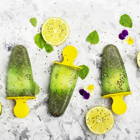 violas: Homemade vegetarian ice cream popsicle fruit citrus peppermint juice with chia seeds is decorated with edible flowers of garden violas in trendy colors