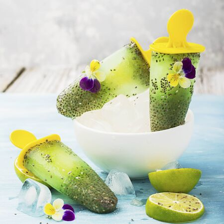 violas: Magnificent homemade yellow-green fruit vegetarian lactose-free ice cream with chia seeds, fruit juice, limes with edible flowers and garden violas on a light background