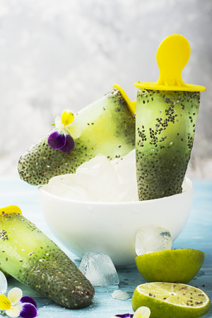 violas: Magnificent homemade yellow-green fruit vegetarian lactose-free ice cream with chia seeds, fruit juice, limes with edible flowers and garden violas on a light background.