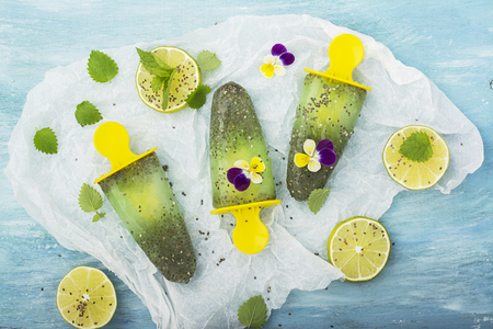 violas: Homemade vegetarian ice cream popsicle fruit citrus peppermint juice with chia seeds is decorated with edible flowers of garden violas in trendy colors. Stock Photo