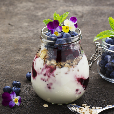 smoother: Healthy breakfast in a glass jar: yogurt, berry puree, whole grain cereal cereal, edible flowers, blueberries on a dark background. The concept of proper nutrition.