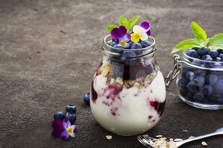 Healthy breakfast in a glass jar: yogurt, berry puree, whole grain cereal cereal, edible flowers, blueberries on a dark background. The concept of proper nutrition Stock Photo