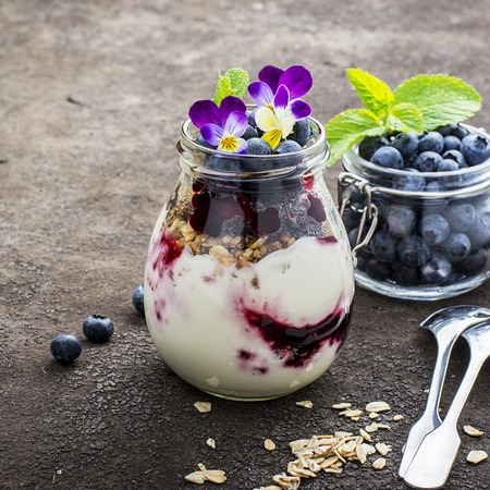 smoother: Healthy breakfast in a glass jar: yogurt, berry puree, whole grain cereal cereal, edible flowers, blueberries on a dark background. The concept of proper nutrition Stock Photo