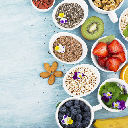 banana: Ingredients for a healthy breakfast, nuts, oatmeal, honey, berries, fruits, blueberry, orange, Edible flowers, Chia seeds, flax seeds, goji berries, almonds walnuts The concept of natural organic food Top view