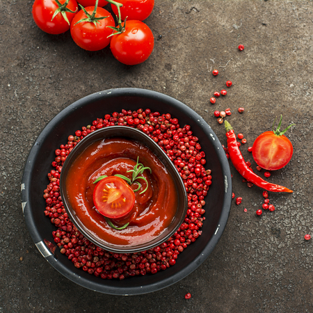 spice: Dark ceramic bowl with tomato sauce, fresh vegetables, herbs, pepper on a dark background. Top View