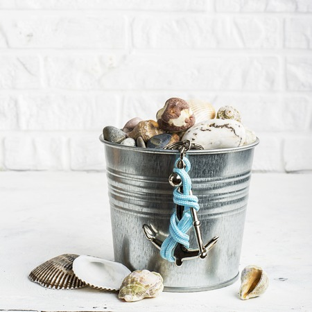 Interior pail full of sea stones for decoration or hand-made articles in marine style with a silver decorative anchor on a white brick wall background. Selective focus Stock Photo