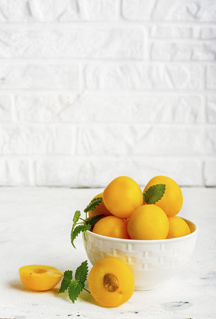 Yellow plums in a white ceramic bowl against a white kitchen brick wall. Selective focus