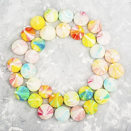 Multicolor bright little merengue on a simple gray trendy background. Top View
