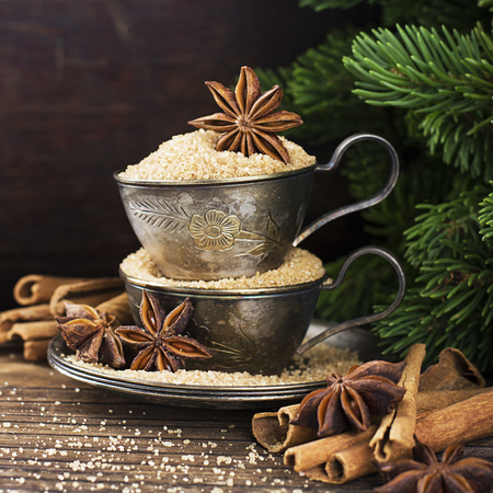 Melchior vintage cups with cane sugar, anise stars, Indian Indian cinnamon sticks on an aged wooden background surrounded by spruce spruce branches. Toned, with imitation of falling snow. Selective focus. Christmas decorations. Stok Fotoğraf - 83424244