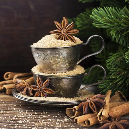 Tazze vintage Melchior con zucchero di canna, stelle di anice, bastoncini di cannella indiano indiano su uno sfondo di legno invecchiato circondato da rami di abete rosso attillato. Tonica, con l'imitazione della neve che cade. Messa a fuoco selettiva Decorazioni natalizie.