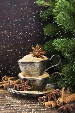 Melchior vintage cups with cane sugar, anise stars, Indian Indian cinnamon sticks on an aged wooden background surrounded by spruce spruce branches. Toned, with imitation of falling snow. Selective focus. Christmas decorations.