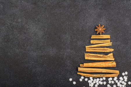 Atmospheric New Year Christmas fir tree from fragrant sticks of Indian cinnamon and anise star on a dark background. Top View.
