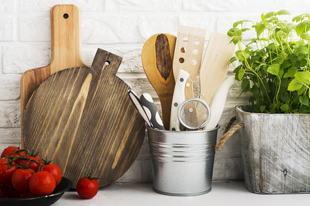 Kitchen still life on a white brick wall background: various cutting boards, tools, greens for cooking, fresh vegetables. Selective focus. Stock Photo